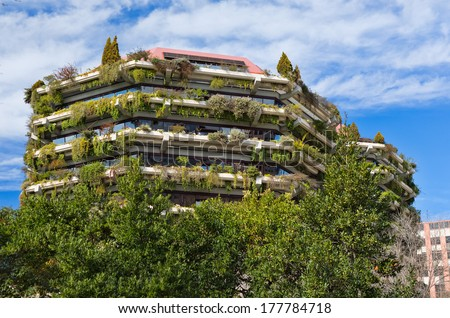 Facade of a building with greenery and flowers on a background of blue sky with clouds. - stock photo