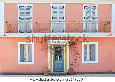 Facade of a lovely greek house with flowers and balcony - stock photo