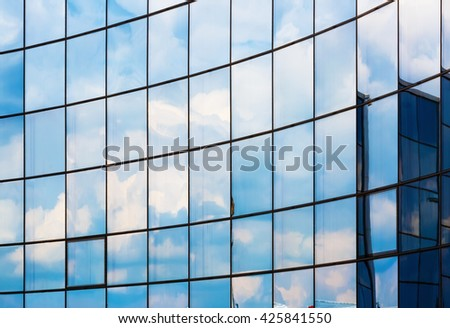 Facade of a modern office building. Modern industrial building with glass. Reflection of blue sky with clouds in the windows. - stock photo