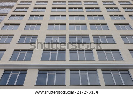Facade of a multistory building with windows - stock photo