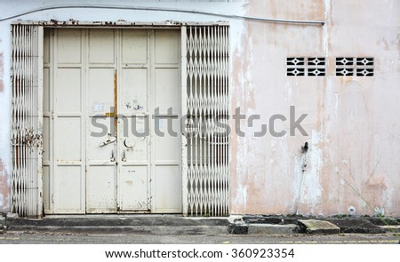 Facade of a pink building wall with sliding metal door.