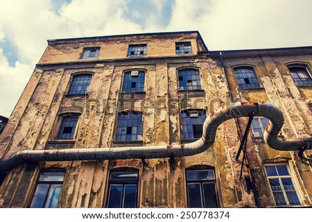 Facade of abandoned textile factory. Vintage filter. - stock photo