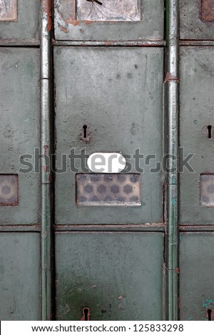 Facade of an old aging metal postal box cabinet door with a blank label for text. - stock photo