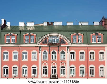 Facade of an old building with a mansard roof. Windows and pink walls
