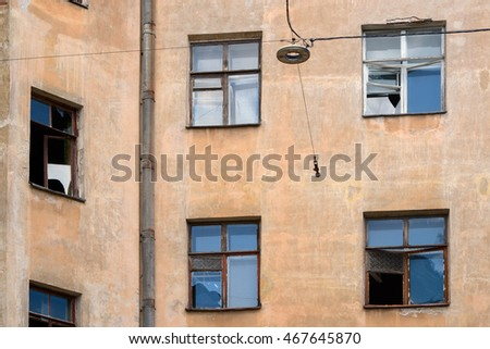Facade of an old house with broken windows and drainpipe, close-up