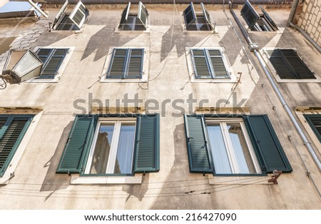 Facade of an old stone house with balconies and shutters in the Venetian style in the town of Kotor. Montenegro - stock photo