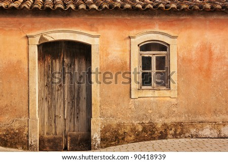 Facade of antique ruined house with roof - stock photo