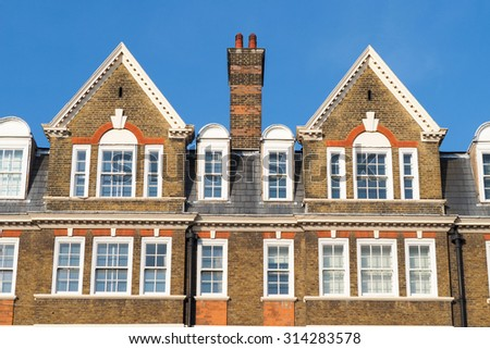 Facade of buildings in London with traditional roofs and a chimney - stock photo