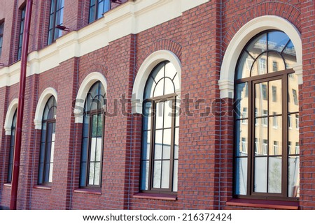 Facade of business center office building made of red brick with parking lot  - stock photo