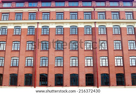 Facade of business center office building made of red brick with parking lot