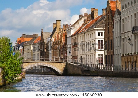 Facade of flemish houses and canal in Brugge - stock photo