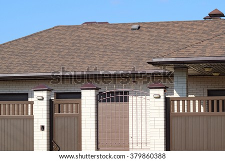 Facade of housing in the same style. Beautiful tile on the roof and the fence brown. - stock photo