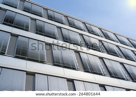 Facade of modern high-rise office building with covered windows Venetian blinds against blue sky - stock photo