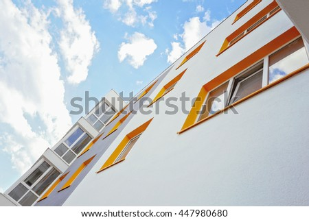 Facade of new residential building with balkony. Modern apartment building and blue sky. - stock photo