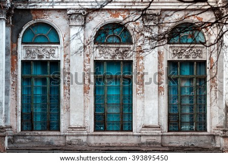 Facade of old abandoned building with large arched windows and columns - stock photo