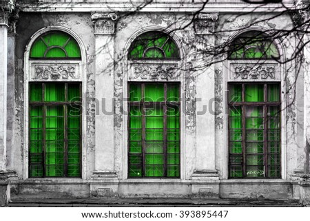 Facade of old abandoned building with three large arched windows of green glass. Monochrome background
