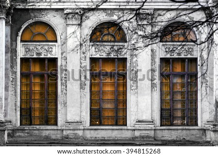 Facade of old abandoned building with three large arched windows of orange glass. Monochrome background - stock photo