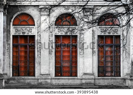 Facade of old abandoned building with three large arched windows of the red glass. Monochrome background - stock photo