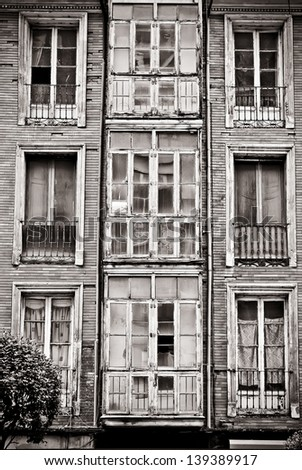 Facade of old building in ruins, black and white