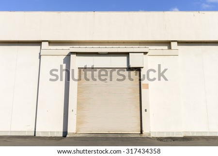 facade of old warehouse with shutter door or rolling door - stock photo