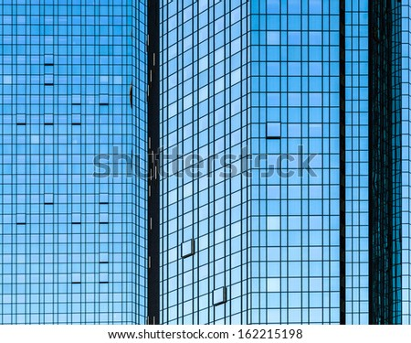 facade of skyscraper with glass front and reflections - stock photo