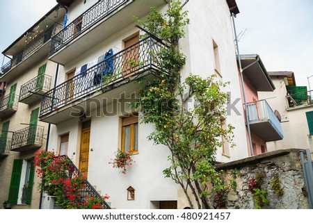 Facade of the house decorated with flowers dekarotivno. Ormea, Italy