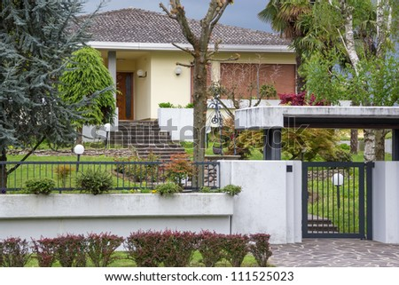 facade of the Italian house with a fence, gate and trees