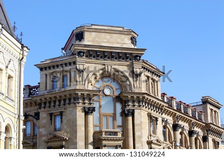 Facade of the massive city building  with a turret - stock photo