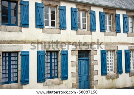 Facade of traditional breton houses with blue shutters, france
