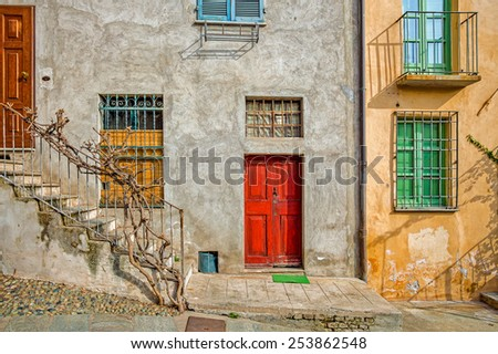 Facade of typical italian house with colorful windows and doors in town of Saluzzo in Piedmont, Northern Italy. - stock photo