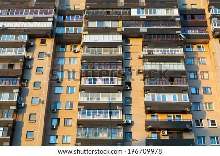 facade of urban apartment house in summer evening - stock photo