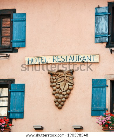 Facade sign of French restaurant with ancient grape decoration - wine specialized traditional restaurant - stock photo