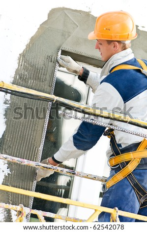 facade thermal insulation works with stopping and trowel - stock photo