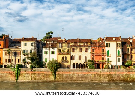 Facades of old houses on waterfront of the Adige River at historic centre of Verona, Italy. Verona is a popular tourist destination of Europe. - stock photo