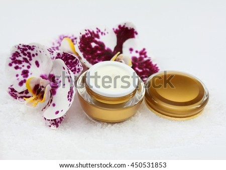 Face and body cream  and orchid with sea salt on white background
