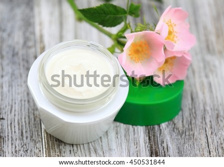Face and body cream  with dog rose, also known wild rose, Rosa canina in  romantic style