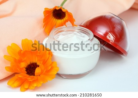 Face and body cream with marigold - stock photo