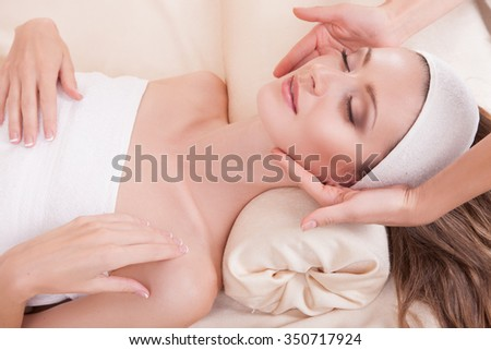 Face and hands.Woman and facial massage. People, beauty, spa, cosmetology and relaxation concept - close up of beautiful young woman lying with closed eyes  - stock photo