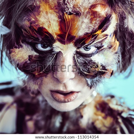 Face art  make up feather mask model look at camera - stock photo