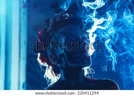 Face art of skull on woman face with smoke outdoors - stock photo