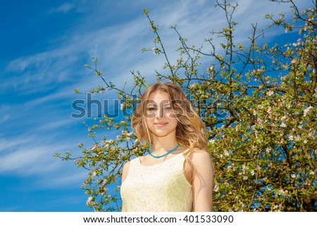 face beautiful sexual girl in the park among flowers. beautiful young girl in the spring garden - stock photo