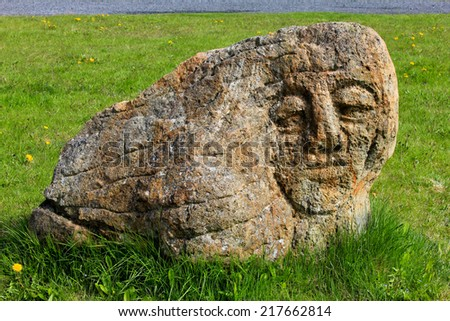 Face carved on a stone - stock photo