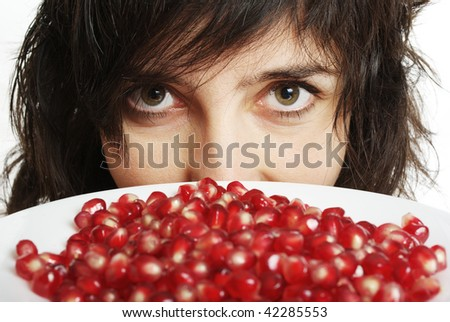 Face closeup of beautiful woman holds pomegranate berries in white plate, isolated on white - stock photo