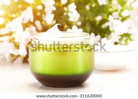 Face cream over flower background - stock photo