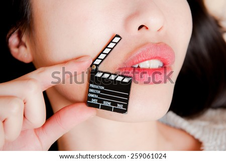 Face detail of sensual woman lips, no eyes, with hand holding little movie clapper board - stock photo