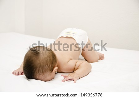 Face down lying baby on bed. - stock photo
