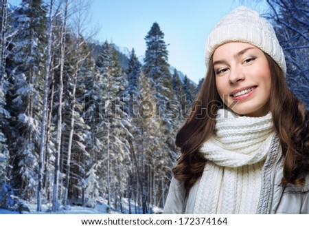 Face girl in winter hat in forest