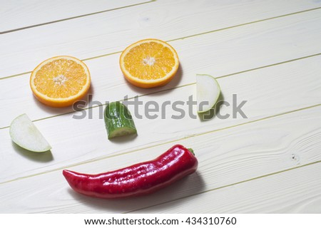 Face made of orange, apple, cucumber and pepper on a kitchen board, on yellow wooden background with copy space. Cheerful face, the concept of healthy eating. - stock photo