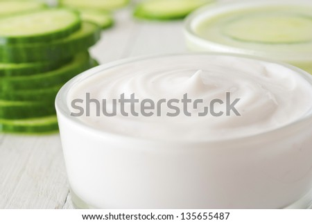 face mask with cucumber slices, white wood background