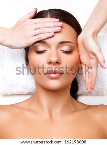 Face Massage. Close-up of a Young Woman Getting Spa Treatment. - stock photo